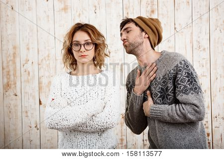 Young handsome man unnerve his girlfriend with crossed arms over wooden background. Copy space.