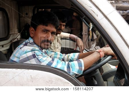 KOLKATA, INDIA - FEBRUARY 10: Man posing on the window of his truck cab in Kolkata, India on February 10, 2016.