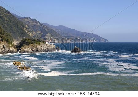 view of the coast of Cinque Terra from Monterosso al Mare in the direction of Vernazza Italy. (You can see the different villages in the mountains)