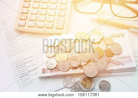 Business, finance savings or mortgage background concept ; Coins, Thai money, pen, calculator, glasses and savings account passbook on white background