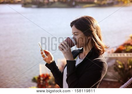 Woman using mobile and drinking coffee tea from paper cup by the lake toning working from home small business concept