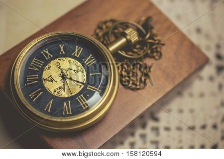 old pocket watch with chain on box wood vintage tone