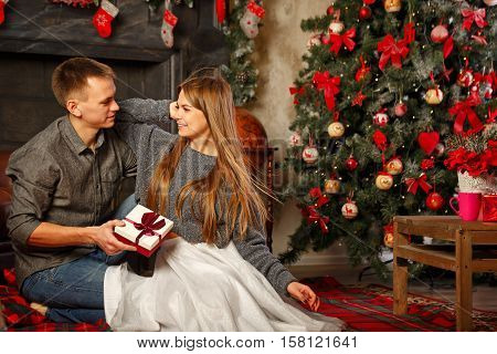 Loving couple and Christmas. The boy gives a girl a Christmas gift. They sit on the floor near the fireplace. In the background a beautiful Christmas tree.
