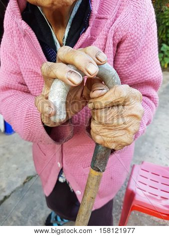 closeup hand of an old asian female pensioner on a walking stick or a cane