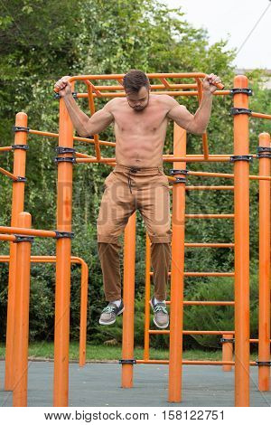 fitness, sport, exercising, training and lifestyle concept - young man doing pull ups on horizontal bar outdoors.