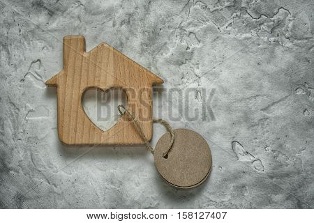 Wooden Toy House With A Blank Tag On Cement Background As A Symbol Of Mortgage