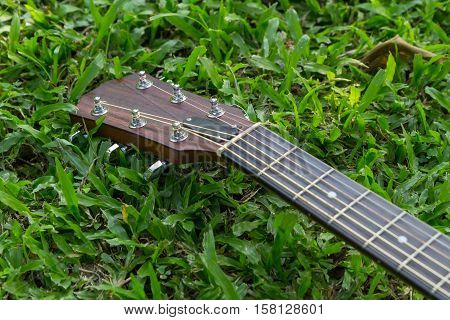 Selective focus to headstock of acoustic guitar on grass