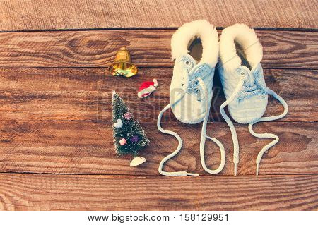2017 new year written laces of children's shoes, christmas decorations on old wooden background. Toned image. Top view.