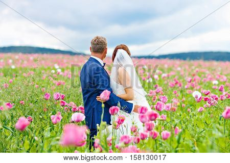 Happy wedding couple in pink poppy field. Beautiful bride, young woman in white dress and oder senior man, groom kissing and having fun in flower field on summer day. Just married, young family.