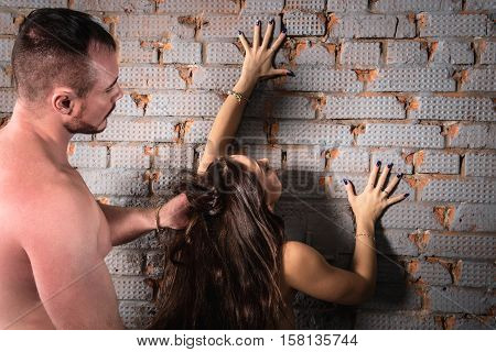 sexy passion couple, man holds woman leaning on the wall.