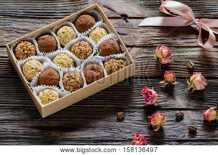 Delicious chocolate truffles, white chocolate truffles and pralines with dry roses, coffee bean and pink gift lace on wooden table. Sweet gift for Valentine's day, Mother's day or Women's day