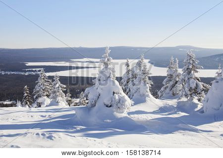 View of the lake from mountain range Zyuratkul winter landscape. Snow swept spruces