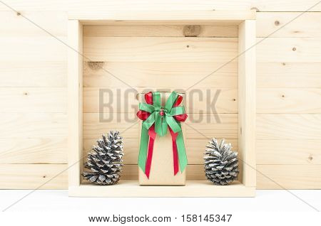 Still life of gift box and pine cones with snow in wooden square box.Christmas decoration. Gift box in wooden pine box.