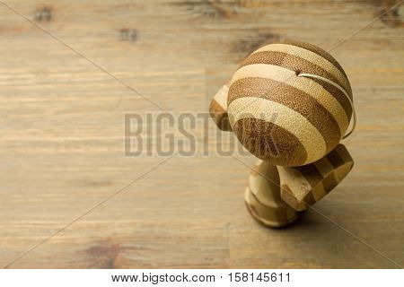 Brown kendama standing on a wooden table. Traditional japanese toy. Accuracy and agility development. Kids, children, ball game, wooden. Striped toy with brown and lightbrown colors. Copyspace. up-and-ball game.