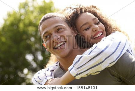 Close up of young adult couple piggybacking outdoors