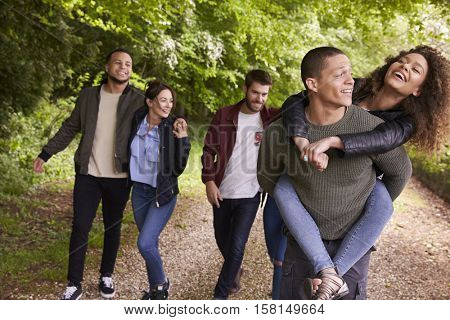Happy friends walking and piggybacking in a country lane