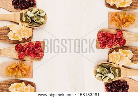 Assortment of dried fruits on wooden spoons on white background. Decorative border of dry exotic fruit. Top view.