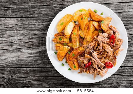 Portion Of Pulled Slow-cooked Meat With Fried Potato Wedges
