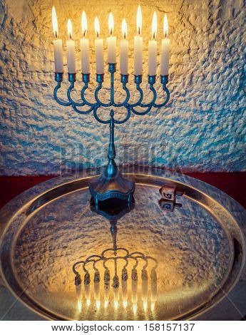 Menorah with the glitter lights of candles and wooden dreidel are traditional Jewish symbols for Hanukkah holiday. Selective focus. Image toned for retro style
