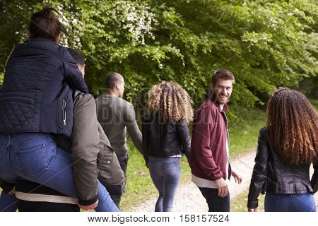 Young adult friends walking in a country lane, back view