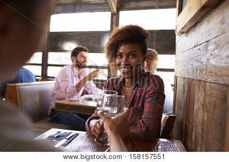 Two female friends making a toast at a table in a bar