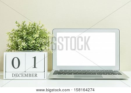 White wooden calendar with black 1 december word with white blank space at center of computer notebook on white wood desk and cream wallpaper textured background selective focus at the calendar