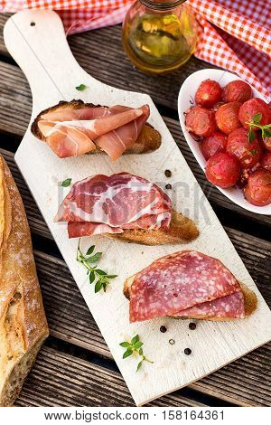 Italian bruschettas with ham prosciutto coppa salami and tomatoes