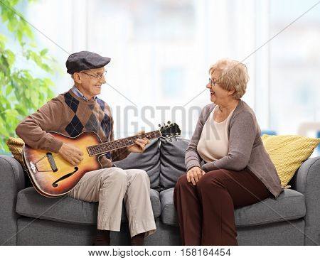 Elderly man sitting on a sofa and playing a guitar to an elderly woman