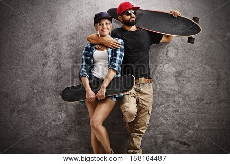 Skaters posing with a longboard and a skateboard and leaning on a rusty gray wall