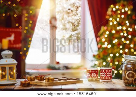 Merry Christmas and Happy Holidays. Time of family tea party. Cups of warm tea with Christmas cookies on wooden table.