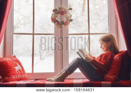 Merry Christmas and happy holidays! Cute little girl sitting by the window and reading a book. Room decorated on Christmas. Kid enjoys the fairy tale.
