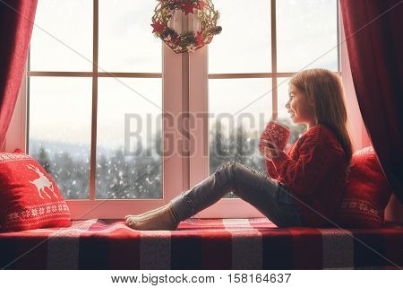 Merry Christmas and happy holidays! Cute little girl sitting by the window with a cup of hot drink and looking at the winter forest. Room decorated on Christmas. Kid enjoys the snowfall.