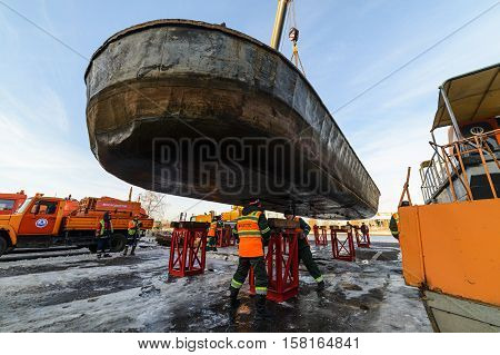 MOSCOW, RUSSIA - NOVEMBER 11, 2016: State Unitary Enterprise Mosvodostok performs recovery vessels on coastal winter parking. Slingers install metal supports.