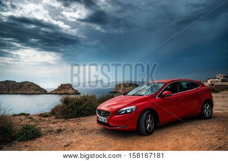 Santa Ponsa, Mallorca, Spain - May 28, 2015: Red car Volvo v40 standing on the edge of a cliff against the dark clouds of the stormy sky. The Mediterranean sea is on a background. Morro d'en Pere Joan bay Es Malgrat rocks in Santa Ponsa Mallorca Spain.