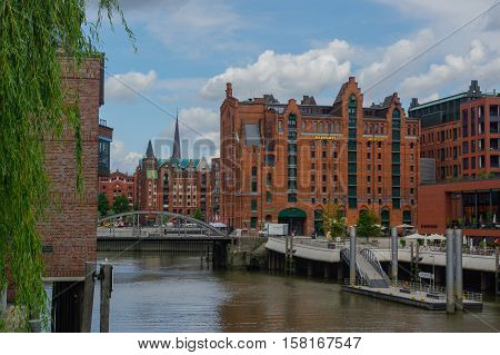 HAMBURG GERMANY - JULY 18 2015: a canal of Historic Speicherstadt houses and bridges at evening with amaising skyview over warehouses famous place on Elbe river.