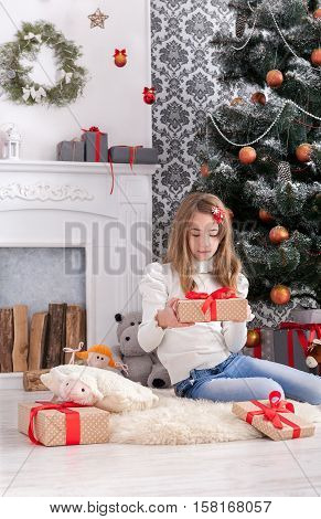 Beautiful happy girl unwrap christmas present box on holiday morning in beautiful room interior. Female child open Xmas gift near decorated fir tree and fireplace. Winter holidays concept