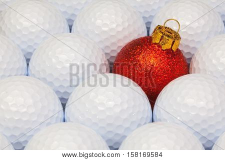 Red Christmas decoration between the white golf balls