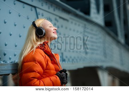 Woman in orange jacket enjoying music on headphones indoors