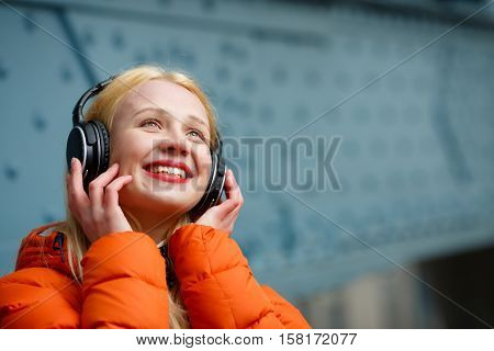 Woman in earphones listening music at blue wall