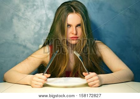 Hungry young woman waiting with an empty plate.