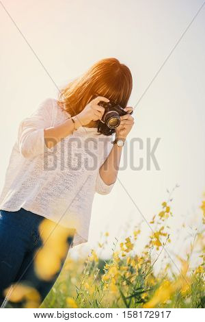 Young woman with camera in the Sunhemp garden sunset