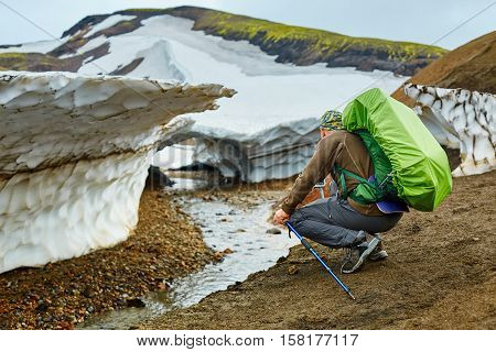 man hiker on the trail in the Islandic mountains. Trek in National Park Landmannalaugar, Iceland. Hiker making photo of glacier near the creek