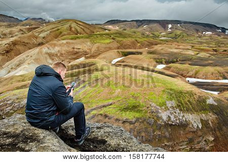 man hiker on the trail in the Islandic mountains. Trek in National Park Landmannalaugar, Iceland