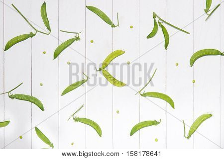 Diet plan menu or program with fresh organic green vegetables. Green peas on white wooden background.
