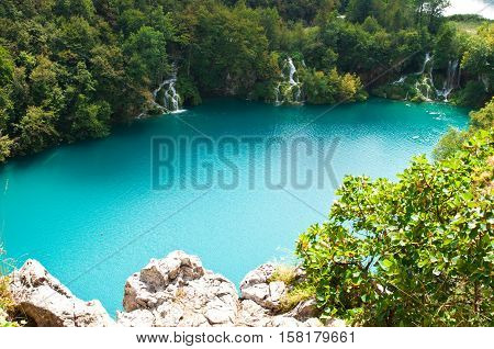 Cascades of Milanovac waterfall among green trees and grass in summer. View from above. Plitvice lakes national park Croatia