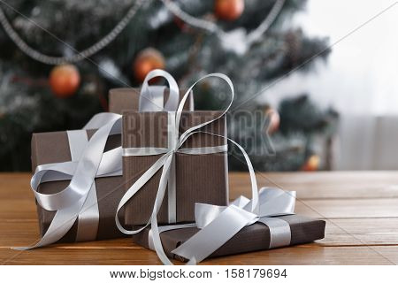 Wrapped elegant present boxes decorated with silver ribbon on table closeup and beautiful decorated christmas tree with ornaments and garland unfocused. Winter holiday gifts background