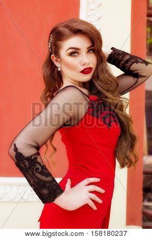 Beautiful young girl in a red evening long dress. The beauty queen in a red dress with long hair