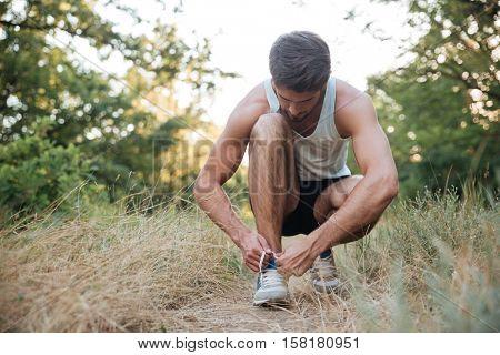 Runner preparing in forest. tying shoelaces