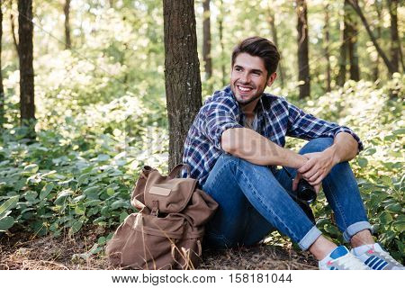 Man sitting in forest near the backpack. looking away. smiling guy