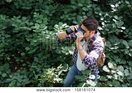 Man looking through binoculars in forest. from above image. stands sideways